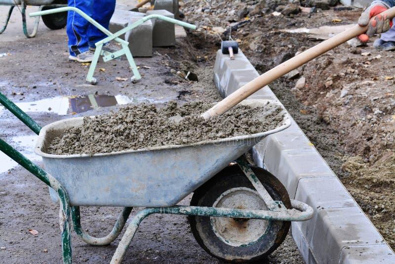 Le pale del lavoratore concrete da una carriola al bordo bloccano l'installazione immagine stock