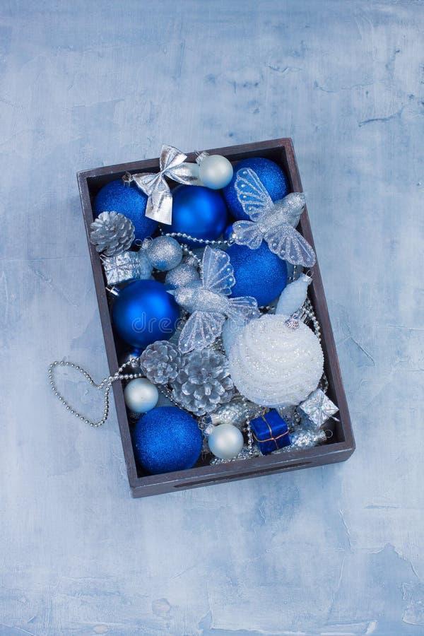 Le palle bianche della decorazione della cartolina di Natale e blu d'argento stabilite gioca i presente dei coni nella scatola di fotografia stock