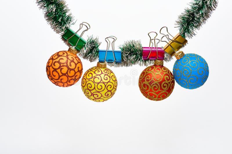 Le palle con gli ornamenti appendono su lamé verde luccicante Lamé con gli ornamenti appuntati di natale, fondo bianco, copia fotografia stock libera da diritti