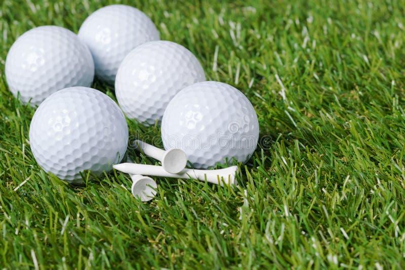 Le palle da golf bianche si trovano su un mucchio di erba verde immagine stock libera da diritti