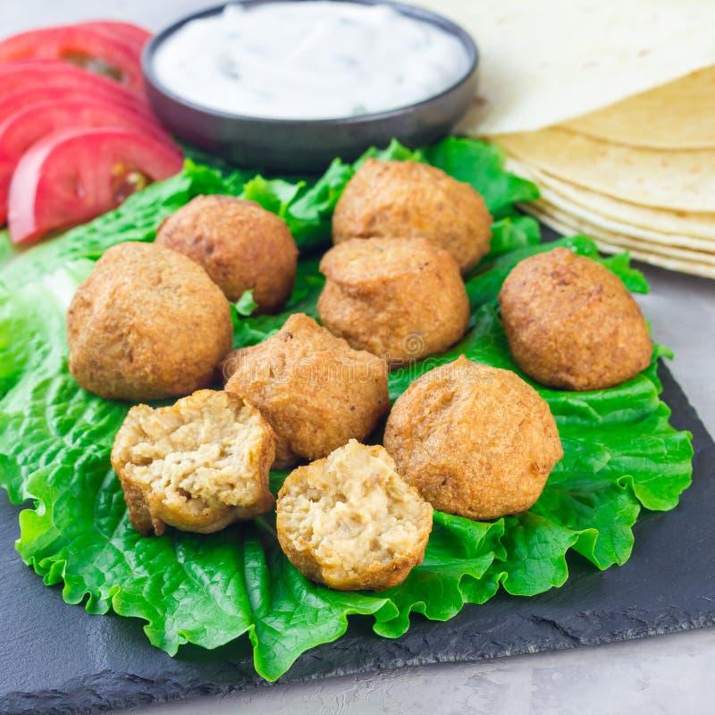 Le palle del falafel del cece sull'ardesia imbarcano con le verdure e la salsa, quadrato immagini stock