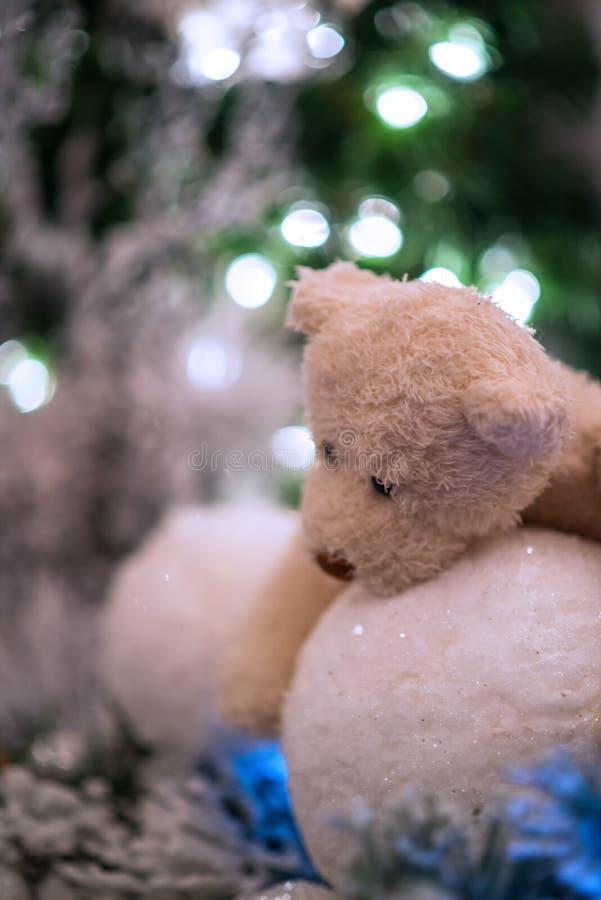 Le palle di neve bianche degli abbracci di orsacchiotto con le luci di natale si rasserenano nei precedenti immagine stock libera da diritti