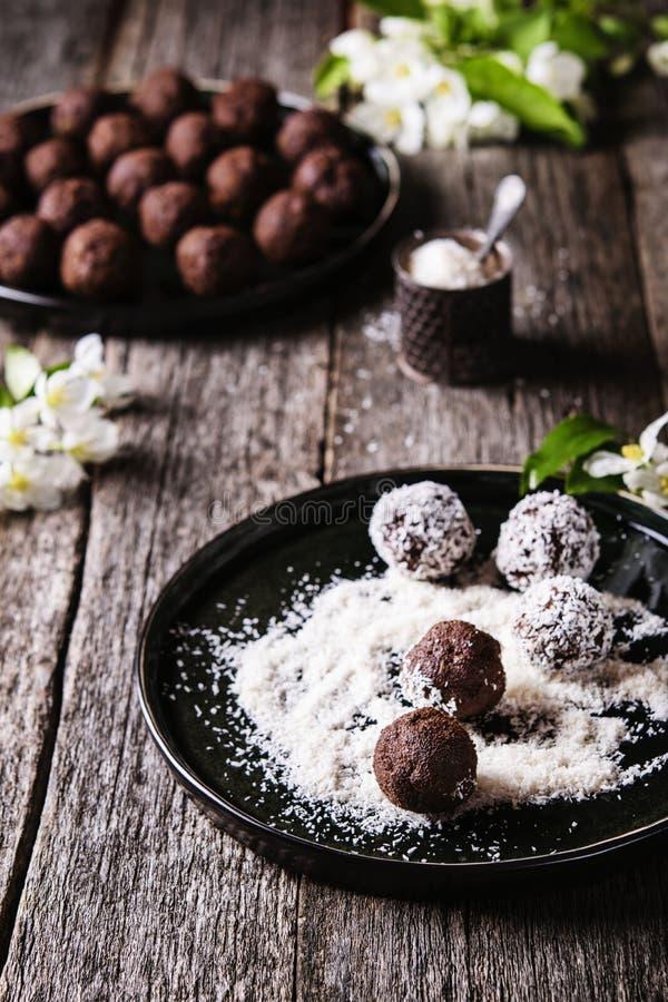 Le palle sane casalinghe del cioccolato del vegano, i tartufi, caramelle hanno spruzzato il cocco grattugiato fotografie stock libere da diritti