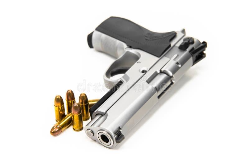 Le pallottole e le pistole, hanno messo sopra un fondo bianco immagini stock libere da diritti