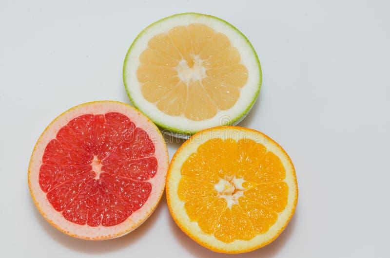 Le pamplemousse rose, l'orange et le bonbon ont coupé dans la moitié photos libres de droits