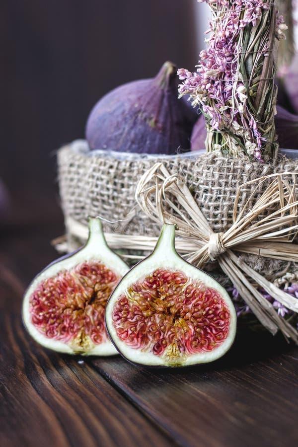 Le panier de la figue porte des fruits avec les moitiés une sur une table images stock