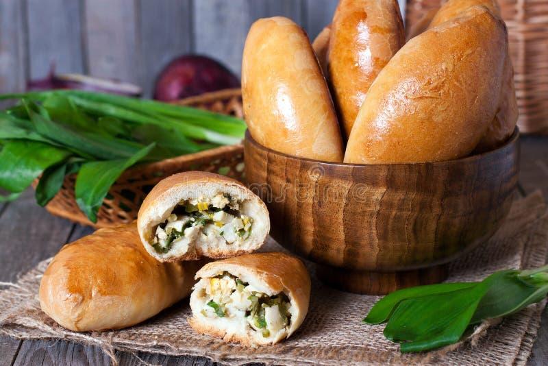 Le panier fait maison des pâtisseries russes (pirogi) a rempli d'oeufs et d'oignon vert images stock