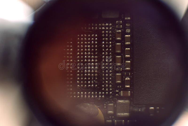 Le panneau électronique du téléphone portable dans le microscope photographie stock