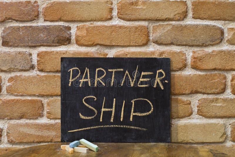 Le panneau de craie avec le mot ASSOCIATION se noient à la main et marquent à la craie sur la table en bois sur le fond de mur de photo libre de droits