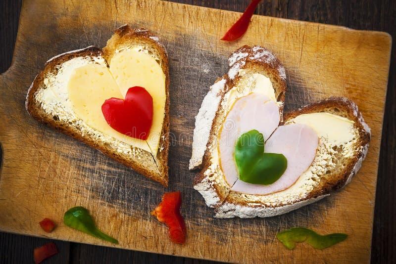 Le panneau en bois de forme de sandwich à coeur poivre la nourriture photographie stock libre de droits