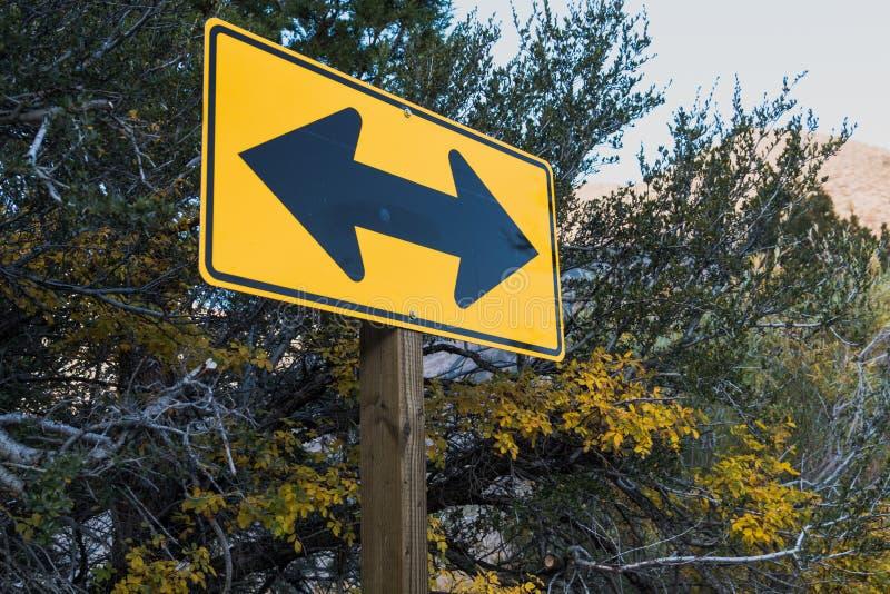 Le panneau routier jaune directionnel de la flèche deux, parmi la chute a coloré des feuilles et un ciel bleu Angle artistique Co photo libre de droits