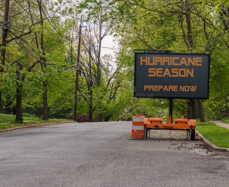 Le panneau routier mobile électronique de Digital qui indique la saison d'ouragan pour préparer maintenant, du côté d'un arbre a  image libre de droits