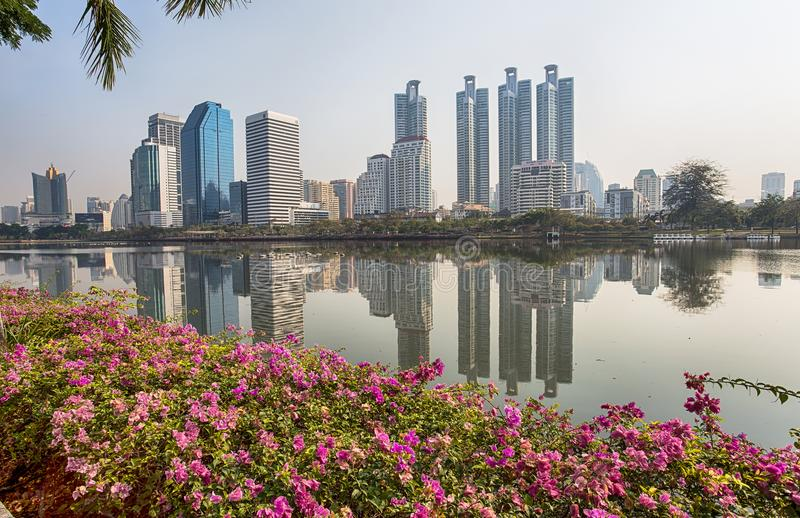 Le panorama du paysage urbain avec des gratte-ciel et le ciel rayent du parc de Benjakitti à Bangkok, Thaïlande image stock