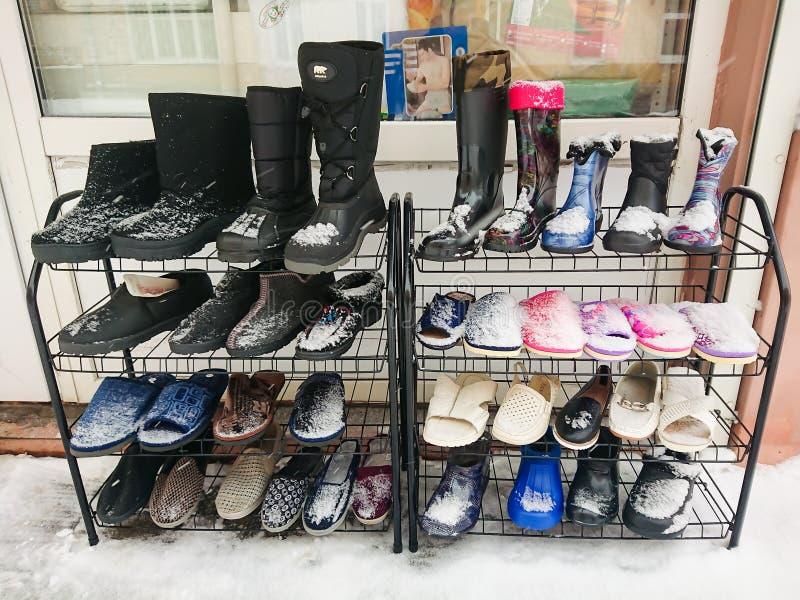 Le pantofole, gli stivali ed altre scarpe sono venduti sulla via Giorno di inverno, neve fotografie stock libere da diritti