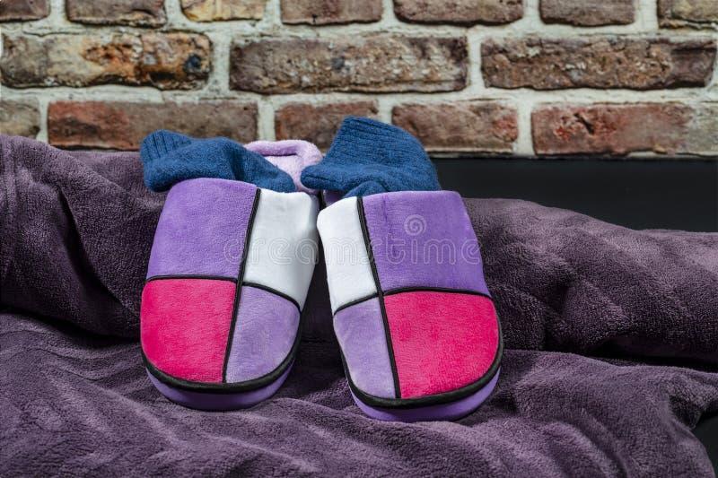 Le pantofole multicolori della donna di inverno con i calzini blu della lana fotografia stock