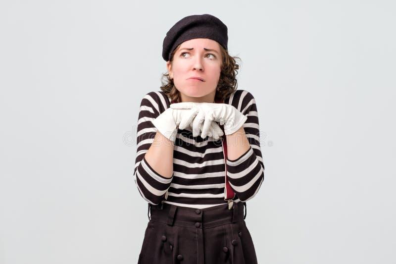 Le pantomime de femme regarde avec le doute étant vers le haut profondément dans les pensées photos libres de droits