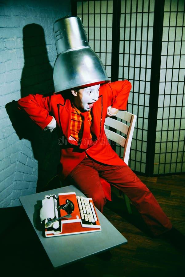 Le pantomime a mis un abat-jour en métal sur sa tête, fait des visages et des poses photo libre de droits