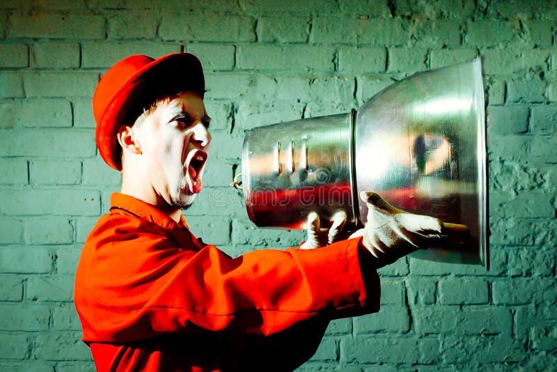 Le pantomime a pris un abat-jour en métal et feint pour crier dans le cri photographie stock libre de droits