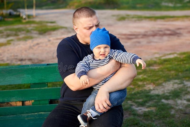 Le papa étreint et embrasse son fils contrarié sur un banc en parc images stock