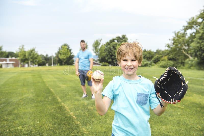 Le papa beau avec son petit soleil mignon jouent le base-ball sur la pelouse herbeuse verte image stock