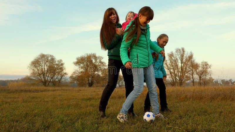 Le papa donne un coup de pied le ballon de football Enfants et football de jeu de maman sur le champ Famille jouant avec le petit photos stock