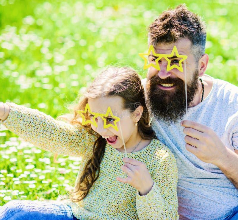 Le papa et la fille s'assied sur l'herbe au grassplot, fond vert Enfant et père posant avec la photo en forme d'étoile d'eyeglase photo libre de droits