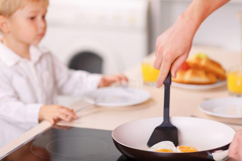 Le papa fait les omelettes pour son fils et lui-même image stock
