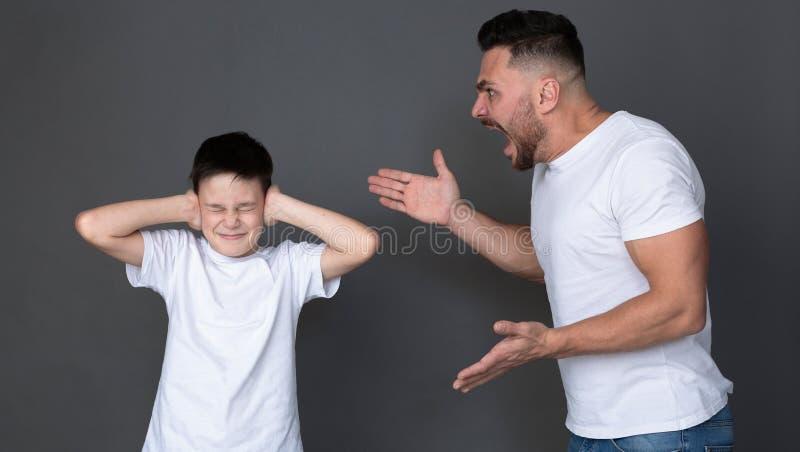 Le papa furieux criant à son fils, enfant effrayé ferment ses yeux et oreilles photographie stock