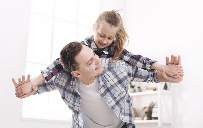 Le papa gai tient sa fille sur le sien de retour photos stock