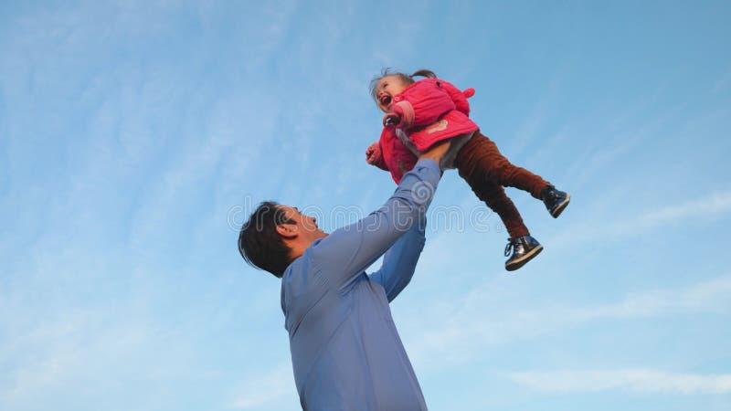 Le papa a jeté le bébé dans le ciel bleu Le papa jette le bébé  Concept de famille heureuse Le papa joue avec sa fille en parc photographie stock libre de droits