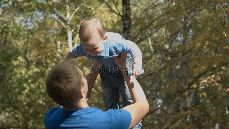 Le papa jette le fils en l'air dans l'air en parc d'automne Famille heureux photographie stock