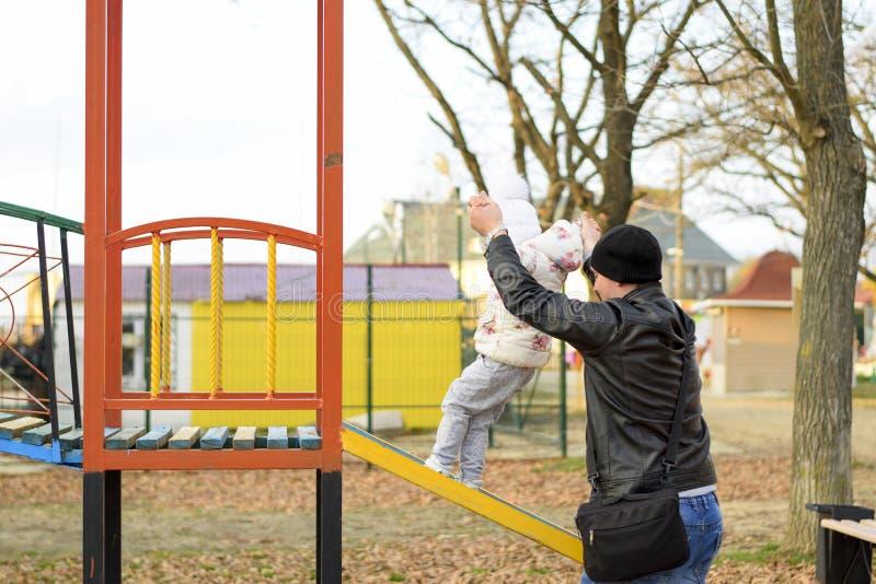 Le papa joue avec sa fille sur le terrain de jeu en parc Promenade d'automne de la famille photo stock