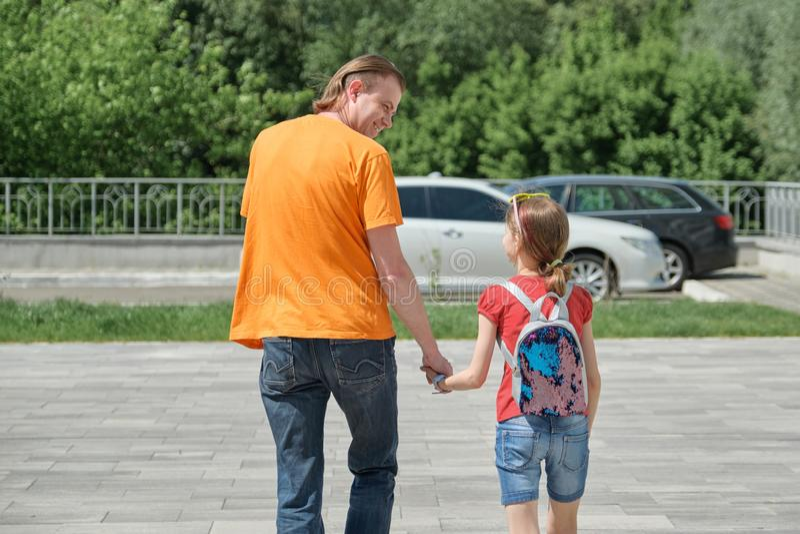 Le papa marche avec sa fille tenant des mains Jour d'été extérieur et ensoleillé, vue arrière photographie stock libre de droits