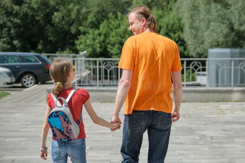 Le papa marche avec sa fille tenant des mains Jour d'été extérieur et ensoleillé, vue arrière photographie stock