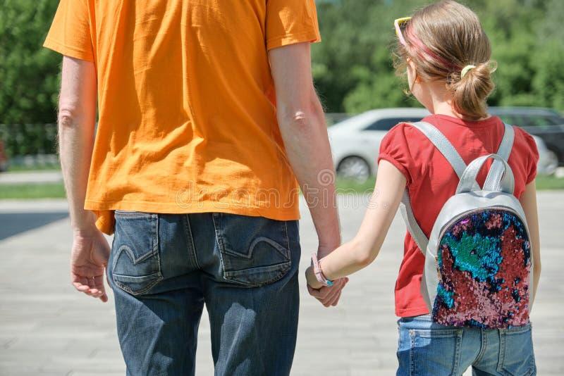 Le papa marche avec sa fille tenant des mains Jour d'été extérieur et ensoleillé, vue arrière photo stock