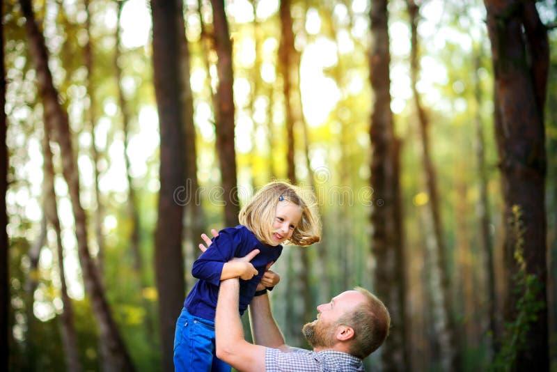 Le papa marche en parc avec sa fille aimée au coucher du soleil, jette sur ses mains image libre de droits