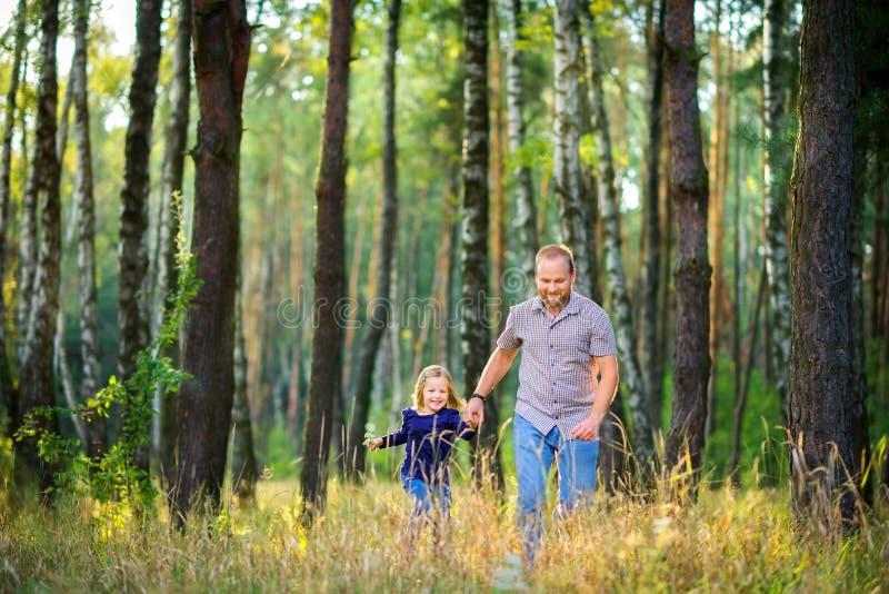 Le papa marche en parc avec sa fille aimée images stock