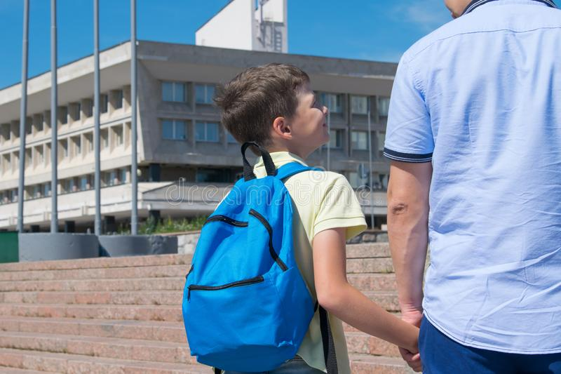 Le papa porte son fils à l'école, regards d'un écolier à son papa image libre de droits