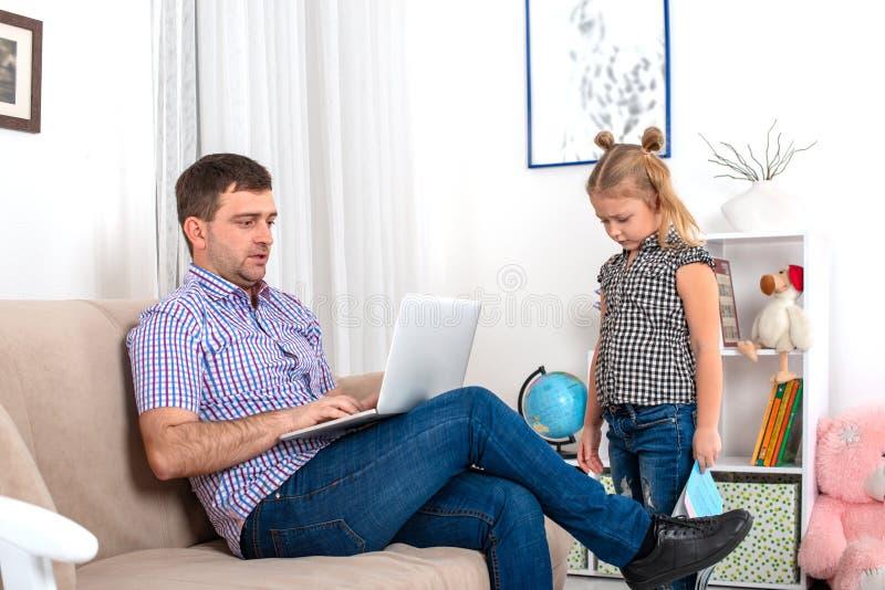 Le papa s'assied sur le divan avec l'ordinateur portable, il est très occupé La fille est ignorée par le père, elle est boulevers photo libre de droits