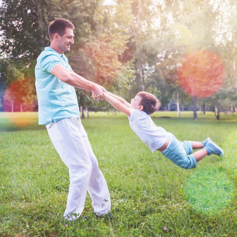 Le papa tourne l'enfant jugeant des mains extérieures images stock