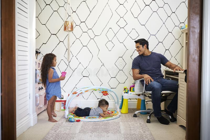 Le papa travaillant à un bureau tourne à la maison autour pour parler à ses jeunes garçons, jouant dans la chambre derrière lui photos stock