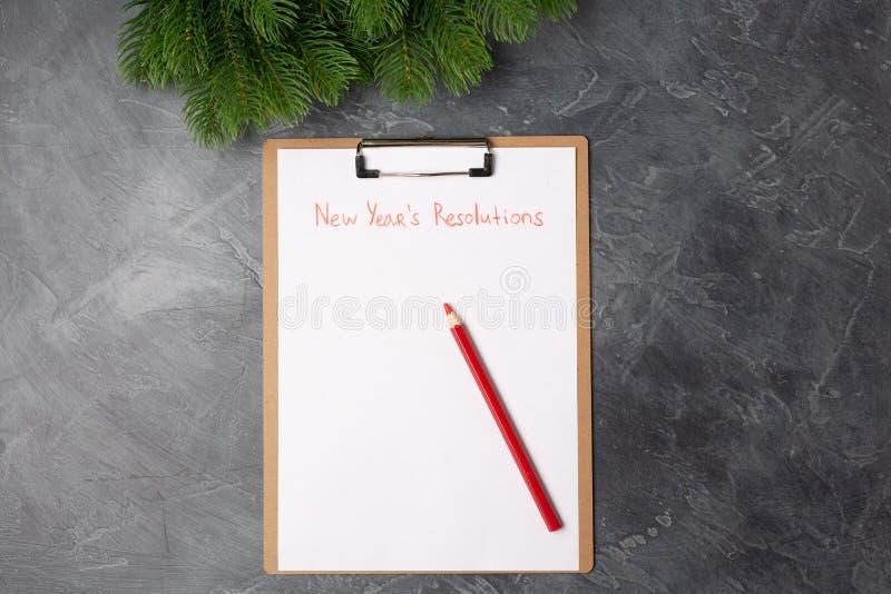 Le papier blanc avec les résolutions de nouvelle année intitulent et crayon rouge sur la table grise Configuration plate Vue supé photographie stock