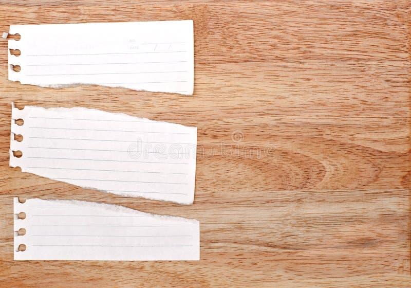 le papier blanc de déchirure est sur le fond en bois image stock