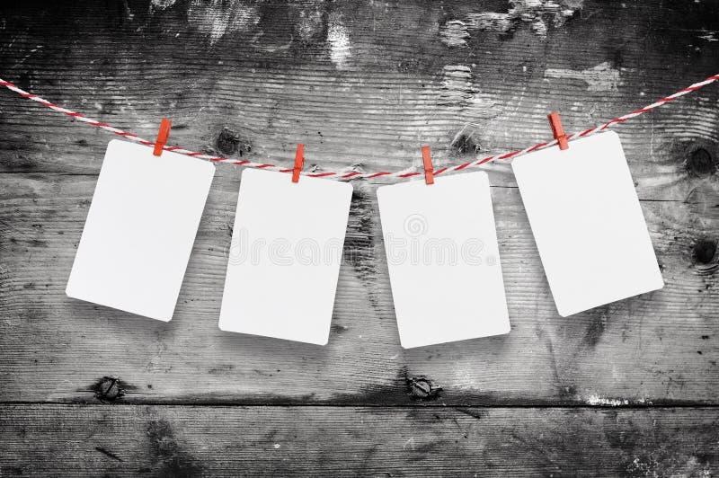 Le papier blanc ou la photo encadre accrocher sur la corde à linge rayée rouge Fond en bois Descripteur pour votre texte images stock