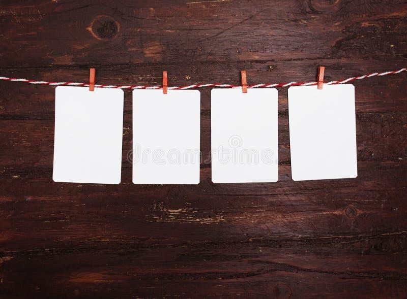 Le papier blanc ou la photo encadre accrocher sur la corde à linge rayée rouge Sur le fond en bois Descripteur pour votre texte image libre de droits
