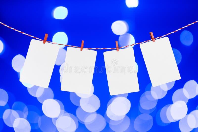 Le papier blanc ou la photo encadre accrocher sur la corde rayée rouge La couleur bleue defocused brouillée allume le fond, calib images stock