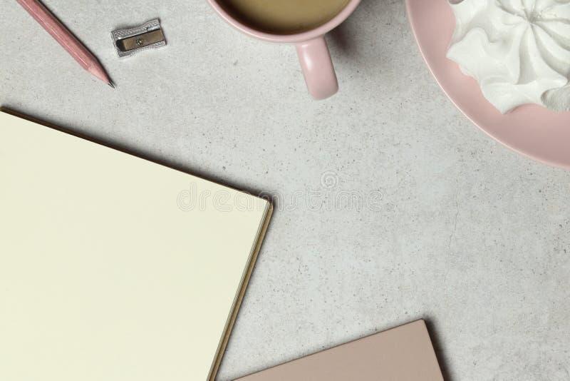 Le papier de carnet, le crayon en bois et affûteuse, une tasse de café avec la guimauve sur le fond de grenat image stock