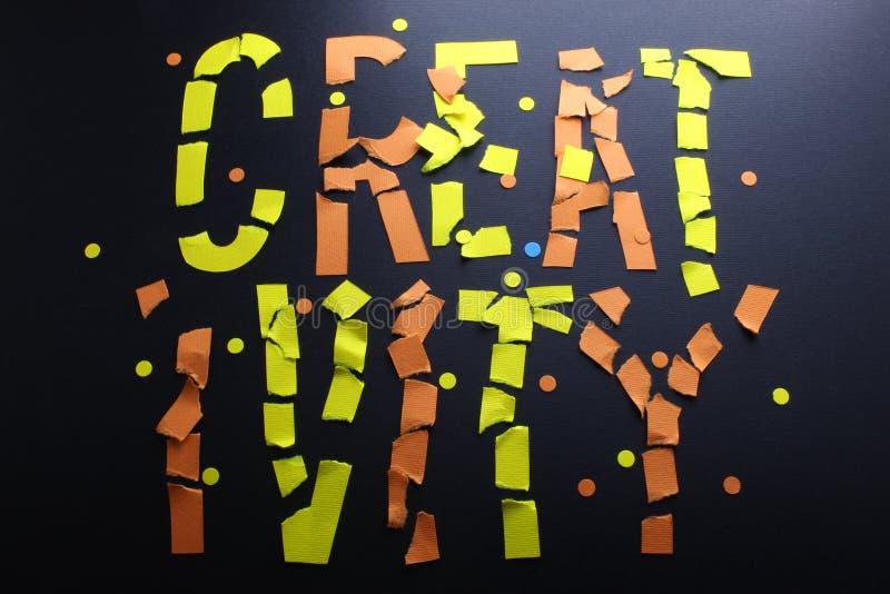 Le papier de créativité a coupé les lettres jaunes oranges en lambeaux sur un fond noir de papier de métier illustration stock