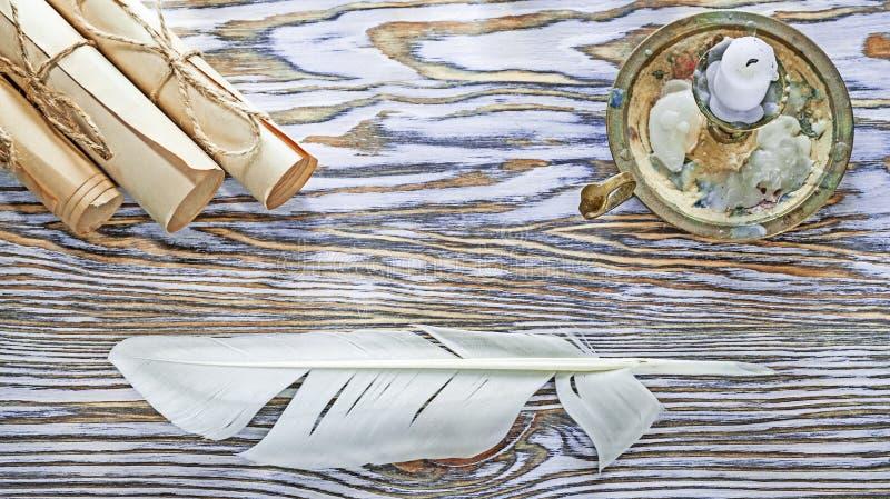 Le papier de vintage roule la bougie de chandelier de plume sur le conseil en bois images libres de droits