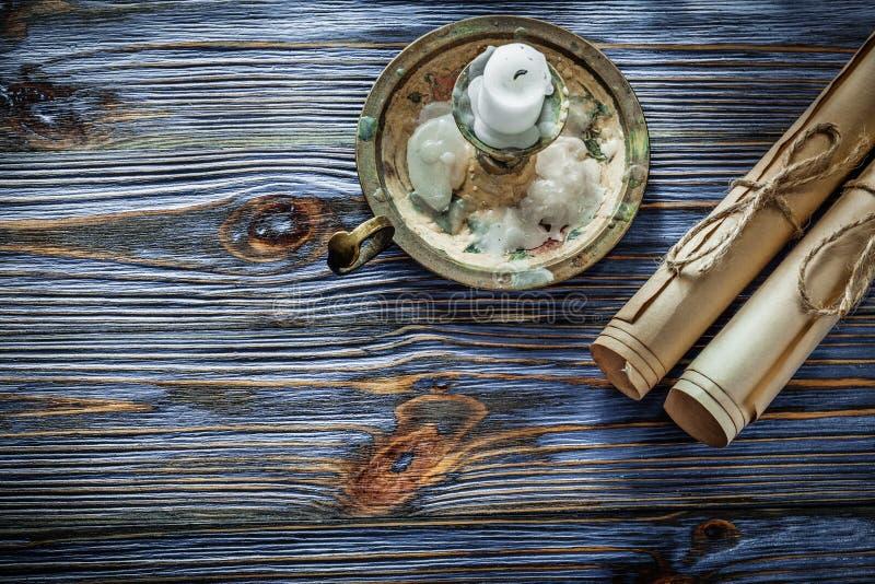 Le papier de vintage roule la bougie de chandelier sur le conseil en bois bleu images libres de droits